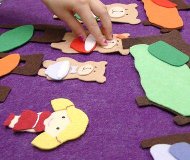 child's hand with goldilocks felt set