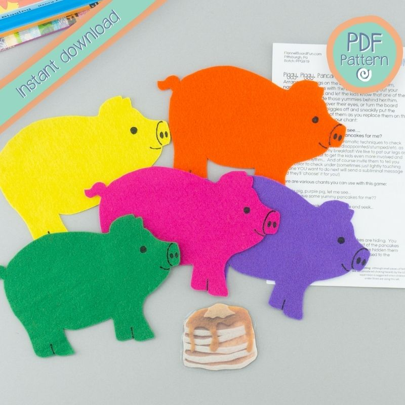 five felt pigs on desk with lyric card and PDF pattern text